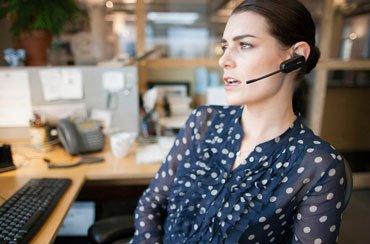 Una empleada llamando con un auricular de Plantronics.