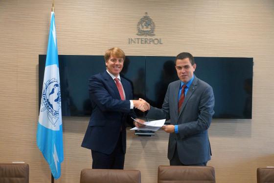 Mark Hughes, de BT, y Silvino Schlickmann, de la Interpol firmando el acuerdo.