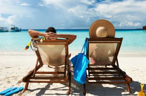 Dos personas toman el sol en una playa.