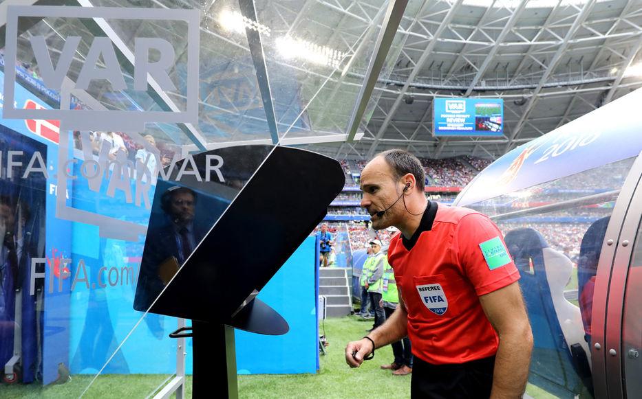 Árbitro observando el VAR en un partido de fútbol.