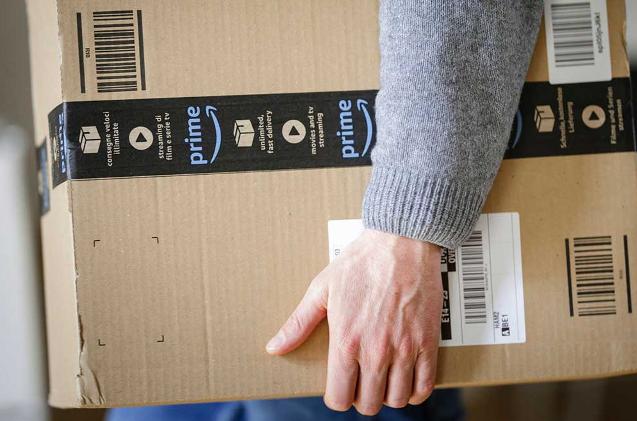 Un usuario porta un paquete de Amazon.