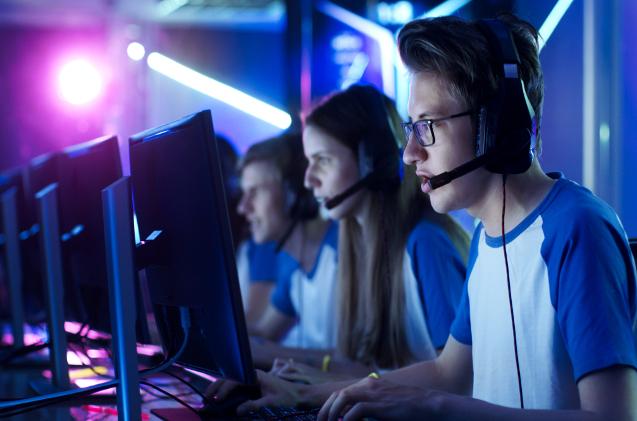 Varios adolescentes juegan en ordenadores.