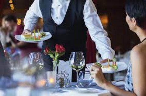 Un camarero sirve a una clienta en un restaurante.