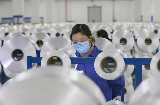 Una operaria se protege del coronavirus en una fábrica.