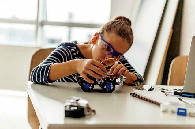 Una niña manipula un pequeño robot.